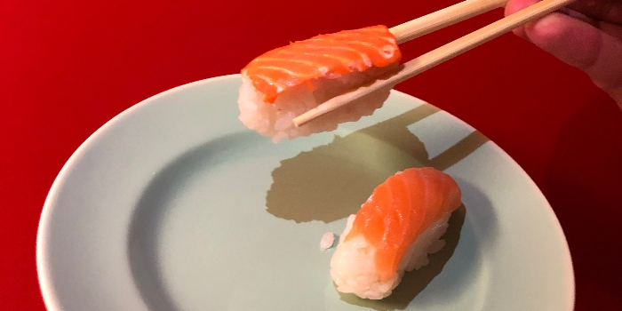 Photo: Printed vegi salmon to the left held with chopstick and real salmon to the right.